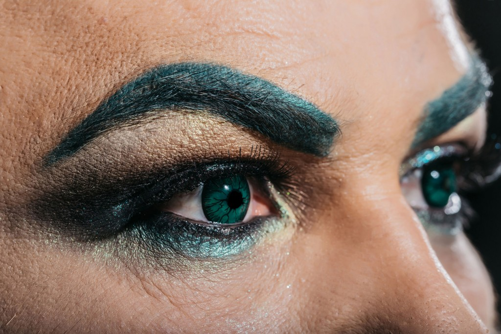 61356327 - two male eyes with dark bright makeup eyeshadow hairy eyebrow and colored decorative green contact lenses closeup