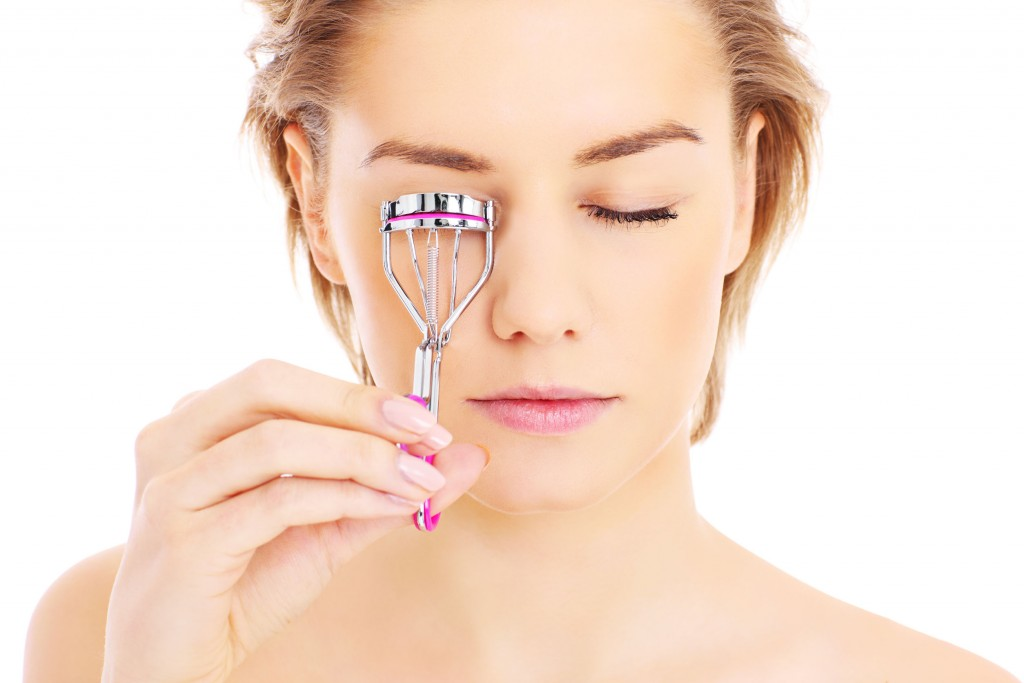25649587 - a picture of a young pretty woman posing with eyelash curler over white background