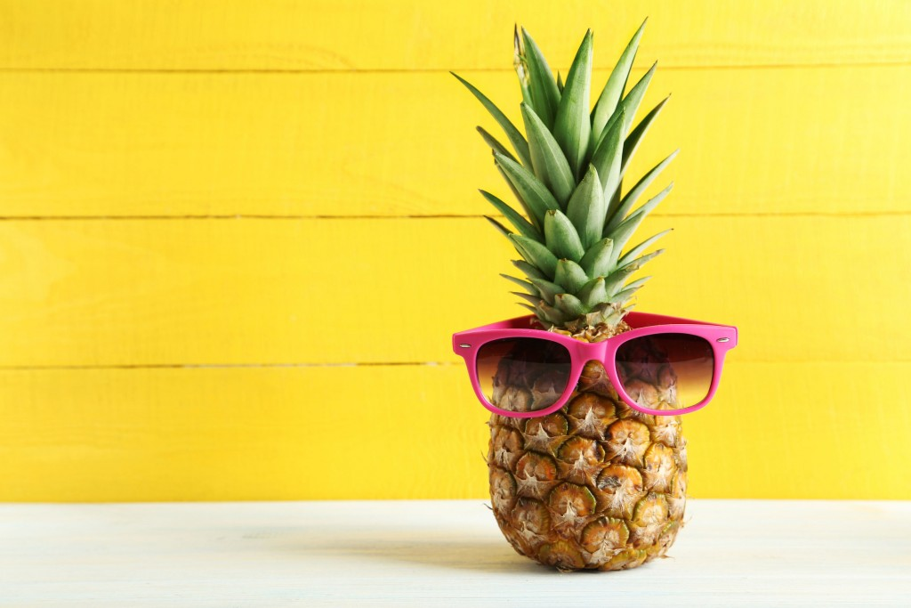 51480514 - ripe pineapple with sunglasses on a white wooden table